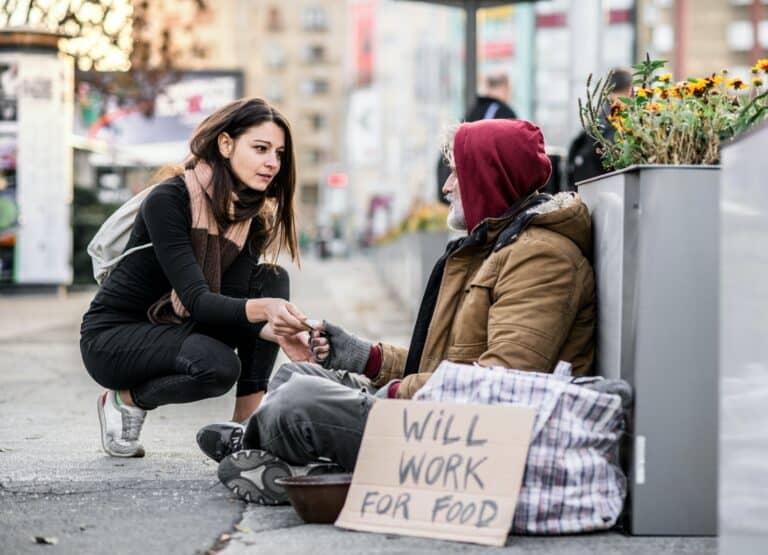 woman gives homeless man money feels good