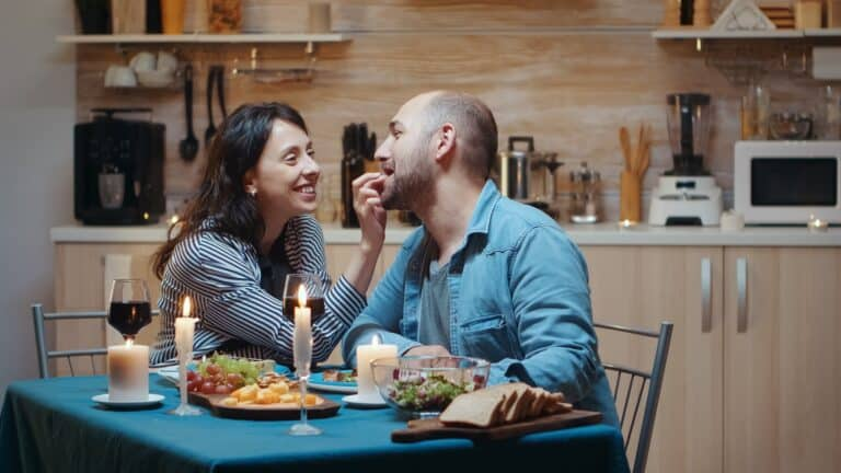 Couple laughing at dinner table at home as laughing is good for the relationship and good for the soul