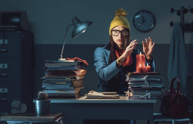 Woman wearing a jacket, yellow hat and a red scarf, dealing with the ups and downs in life as she sits freezing in her office with a pile of work to be done