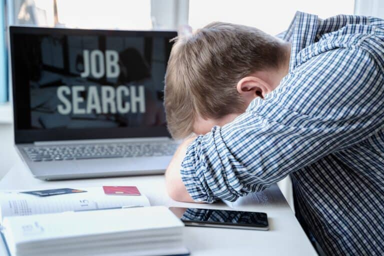 Man lies face down on table next to laptop, losing his confidence for his ability to find the job he wants .