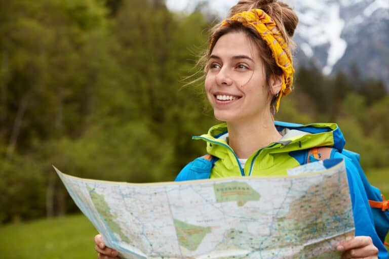 A very satisfied female hiking on a trail with looking at a map as she plans her next direction along her path accepting the ups and downs in life as her journey continues through life