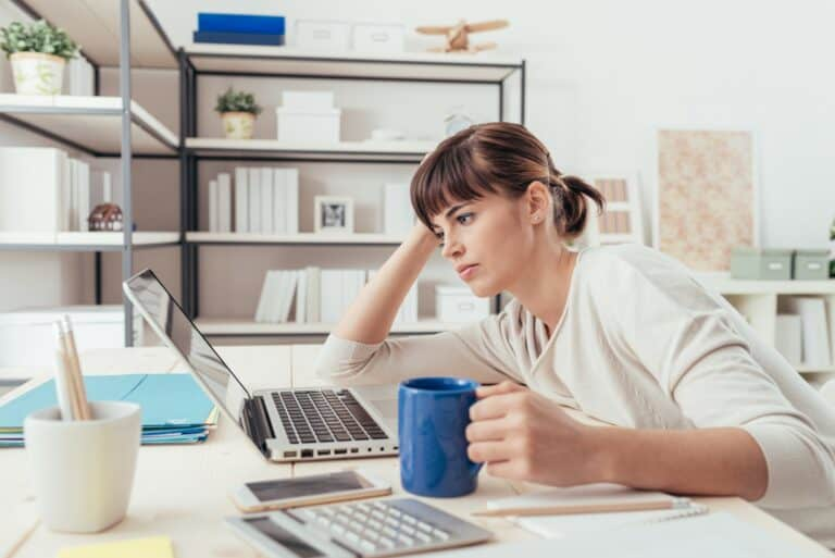woman at laptop with lack of inspiration to move forward