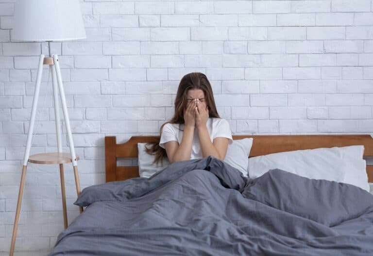 Unhappy young woman crying alone in her bed at home, grieving over loss of loved one