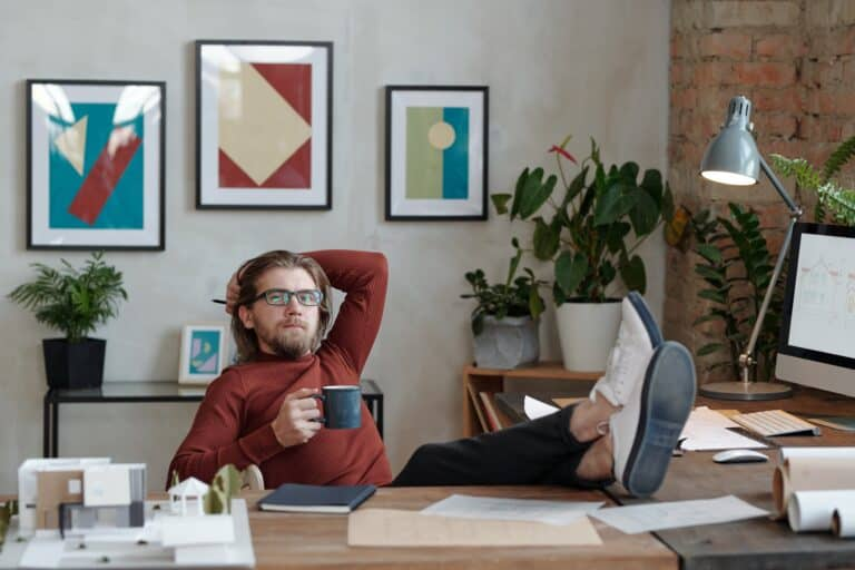 Young relaxed architect with cup of coffee looking at you while thinking of ideas for new project