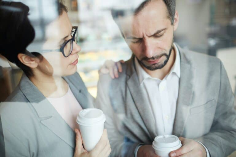 A woman and a man having coffee as she is showing compassion and empathy for his difficult situation